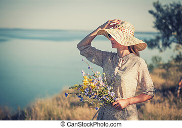 Woman in a hat on a high sea cliff with a bouquet of flowers in a retro hat.