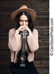 woman in a hat with a ukulele indoors on a wooden wall background