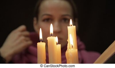 woman in a headscarf doing the magic ritual. close-up several candle and old book. halloween or religion concept