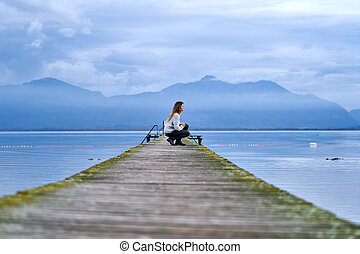 Woman in a jetty facing the lake