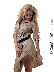 attractive blond wearing a khaki colored dress standing on white