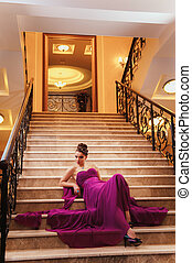 woman in a long dress is sitting on the stairs