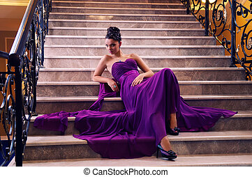 woman in a long dress lying on the stairs