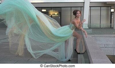 Woman in a long dress standing.