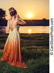 Woman in a long glamorous dress at sunset. Beautiful landscape view, shot from the back