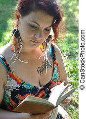 Woman in a meadow reading a book