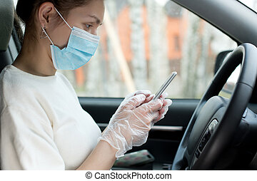 Woman in a medical mask and medical gloves holds a phone sitting in a car