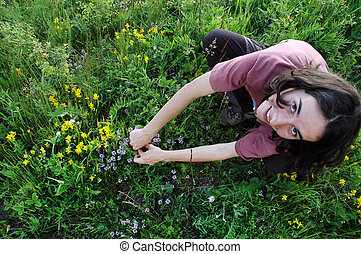Woman in a middle of a meadow full with flowers in spring