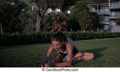 Woman in a park on the grass stretches her legs during fitness.