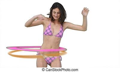 Woman in a pink bikini using a hula hoop against a white...
