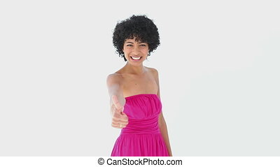 Woman in a pink dress giving the thumb-up against white...
