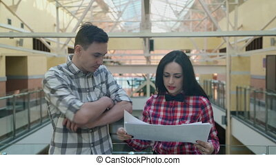 Woman in a pink plaid shirt gives a man the sheets from the stack.