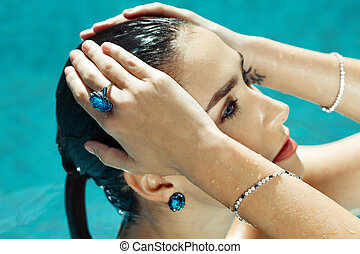 Woman in a pool with large sapphire