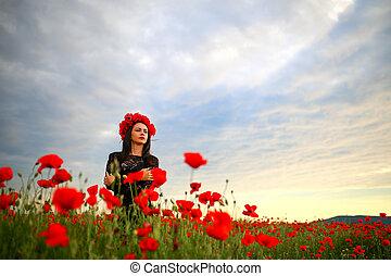 woman in a poppy field in a dress