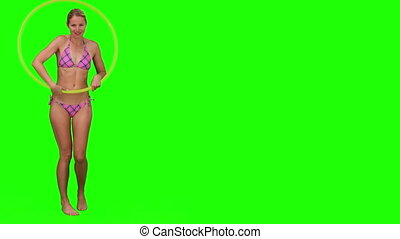 Woman in a purple swimsuit playing with a hoop