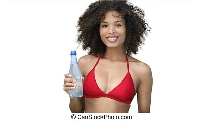 Woman in a red bikini drinking water against a white...