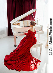 Woman in a red evening dress - A young beautiful woman in a...