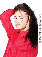 Woman in a red shirt with hands in her black hair