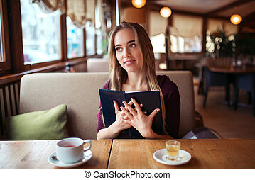 Woman in a restaurant holding menu in hands