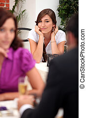 Woman in a restaurant watching another couple