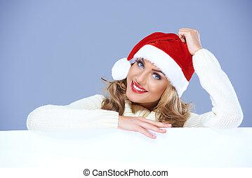 Woman in a santa hat resting on a blank billboard