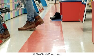 woman in a shoe shop chooses boots tries