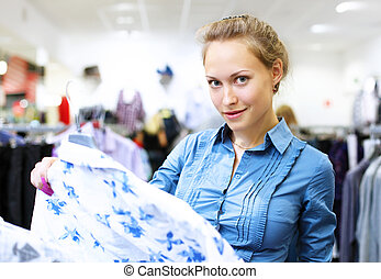 Woman in a shop buying clothes - Young woman in a shop...