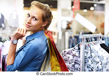 Woman in a shop buying clothes
