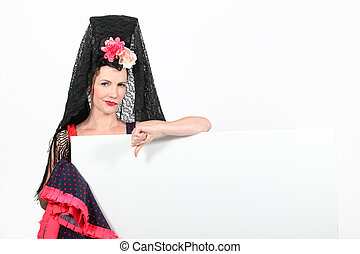 Woman in a Spanish outfit giving the thumbs down to a board left blank for text