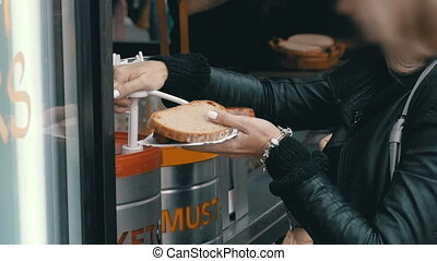 Woman in a Street Cafe Smears Ketchup on a Hot Dog. Prague, Czech Republic