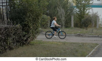 Woman in a striped blouse is riding a bicycle.