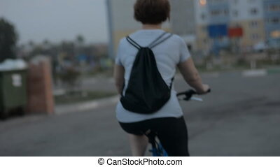 Woman in a striped blouse rides a bicycle in the evening...