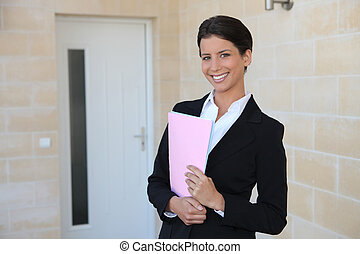 Woman in a suit standing outside a front door