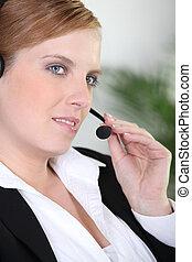 Woman in a suit using a telephone headset