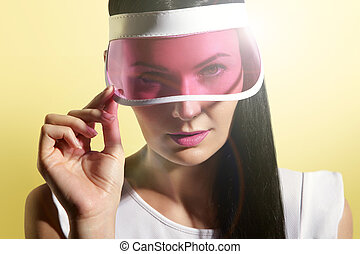 woman in a sun visor on a sunny yelow background