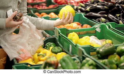 Woman in a supermarket at the vegetable shelf.