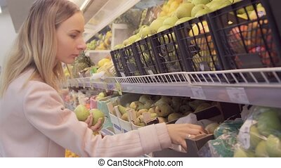 Woman in a supermarket at the vegetable shelf shopping for groceries, he is checking out the groceries
