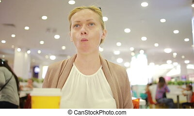 woman in a supermarket drink coffee. chewing food - woman in...