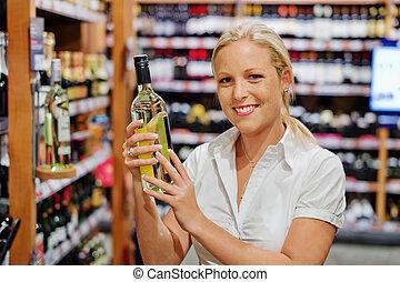 woman in a supermarket wine shelf - a woman buys wine in a...