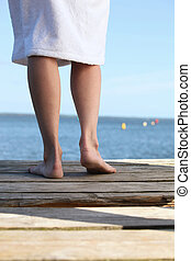 Woman in a toweling robe standing barefoot on a wooden jetty