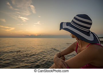 Woman in a trendy straw sunhat relaxing on a beach looking out over the  ocean