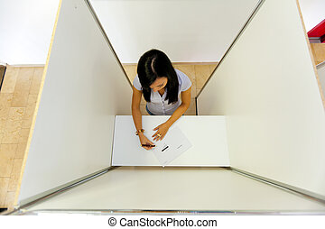 Woman in a voting booth - Young woman in a polling booth in...