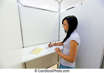 Woman in a voting booth - Young woman in a voting booth