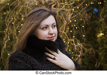 Woman in a warm coat on the background of lights