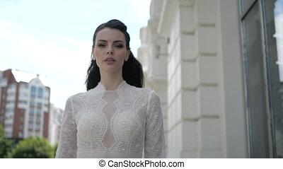 Woman in a wedding dress is walking down the street