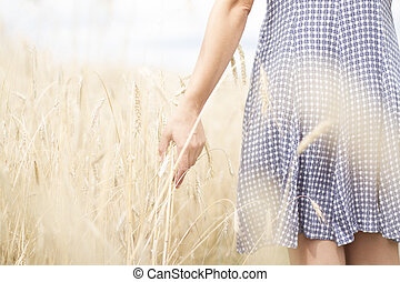 Woman in a wheat field in the sunset
