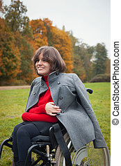 woman in a wheelchair - idle invalid for a walk in the...