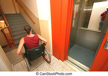 woman in a wheelchair in the stairwell - a woman in a...