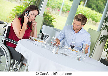 woman in a wheelchair on the phone at a restaurant