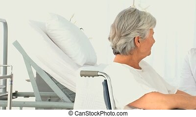 Woman in a wheelchair talking to her doctor